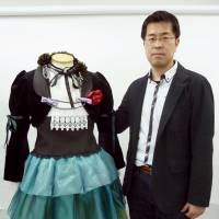 Minoru Okamoto, president of S.H.C. Japan Co., unveils a made-to-order costume produced by online store Cosplay Costumes Japan on May 29. | KYODO