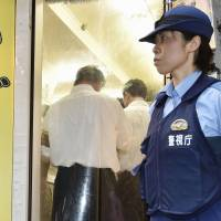 A Metropolitan Police Department officer guards the entrance to a 'dappo' herb shop during an inspection Thursday in Shinjuku Ward's Kabukicho entertainment district. | KYODO
