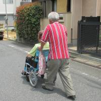 Shigeru Suzuki and his wife, Hiroko, who suffers from Alzheimer's disease, walk through their neighborhood in Kitaurawa, Saitama Prefecture, earlier this month. | TOMOKO OTAKE