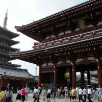 Tourists take in Sensoji Temple's five-story pagoda and Hozomon Gate in Taito Ward, Tokyo. | SATOKO KAWASAKI