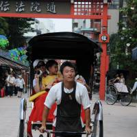 Rickshaw man Koshiro Isshiki takes tourists from Singapore for a spin. | SATOKO KAWASAKI