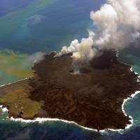 A newly created islet (right) and the original Nishinoshima Island (left) are shown joined by erupting lava on Wednesday in the Pacific Ocean 1,000 km south of Tokyo.  | JAPAN COAST GUARD/AFP-JIJI