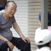 Kaoru Ishiyama, 82, chats with other people as they wait July 11 for an orthopedic clinic in Kawasaki to open for the day. | BLOOMBERG