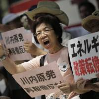 Demonstrators in Tokyo protest on Wednesday against the NRA's preliminary approval of reactor restarts at the Sendai plant. | AP