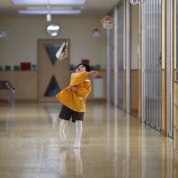 A boy plays with a paper airplane in the corridor of the Emporium kindergarten in Koriyama, Fukushima Prefecture, in February. | REUTERS