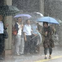 A woman walks through torrential rain in Fukuoka on Monday morning. | KYODO