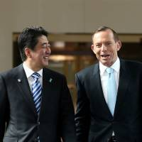 Prime Minister Shinzo Abe walks with Australian counterpart Tony Abbott after he addressed a joint sitting at Parliament House in Canberra on Tuesday. | REUTERS