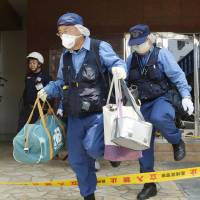 Police investigators leave an apartment building Monday in Sasebo, Nagasaki Prefecture, where a 15-year-old schoolgirl was found murdered over the weekend. | KYODO
