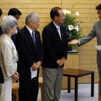 Prime Minister Shinzo Abe receives a petition abduction groups at his official residence in Tokyo on July 4. There is speculation that Abe could use a possible breakthrough on the emotive issue to call a snap election.   REUTERS