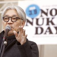 Composer and performer Ryuichi Sakamoto addresses the crowd at the No Nukes Day rally in Tokyo on March 9 as protesters demonstrated against reactor restarts. | KYODO