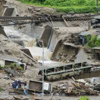 A work crew starts the cleanup process after a flash flood tore through Nagiso, Nagano Prefecture, on Wednesday, destroying at least two houses and ripping away bridges. | KYODO