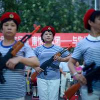 Chinese civilians take part in an event outside a mall in Beijing on Monday commemorating the 77th anniversary of the start of war with Japan. | AFP