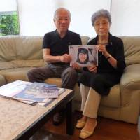 Shigeru and Sakie Yokota hold a portrait of their daughter, Megumi, after an interview in Kawasaki on Wednesday. A new inquiry into Japanese abducted by North Korea offers the Yokotas their best and perhaps final chance of being reunited with the daughter, who was snatched by the North at age 13. | BLOOMBERG