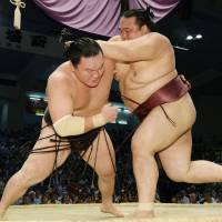 Three's a crowd: Ozeki Kisenosato (right) defeats yokozuna Hakuho at the Nagoya Grand Sumo Tournament on Friday. With the loss, Hakuho (11-2) now sits in a three-way tie for first place with two days remaining in the tournament.   | KYODO