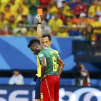 Looking into things: Cameroon's Alex Song is shown a red card after delivering an elbow to the back of Croatia's Mario Mandzukic (right) during their match on June 18. | KYODO