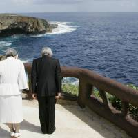 "Silent tribute: The Emperor and Empress bow toward ""Suicide Cliff"" in June 2005,  a rugged location where Japanese civilians committed suicide. 
