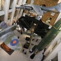A Spitfire fighter plane, Harrier jump jet and V-1 rocket are suspended from the museum's ceiling.   REUTERS