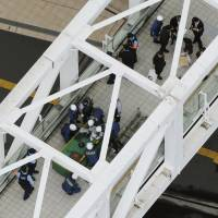 Aftermath of a scene: Tokyo Metropolitan Police scour a pedestrian bridge near the South Exit of Shinjuku Station where a man set himself on fire in an apparent protest on June 29. | KYODO