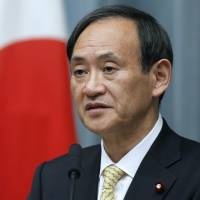 In the hot seat: Chief Cabinet Secretary Yoshihide Suga speaks at a news conference in Tokyo in 2012. | BLOOMBERG