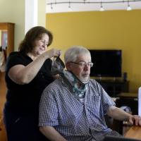 Screen shot: A woman places a brace around the neck of her husband as he sits in front of a laptop he uses for virtual house calls with his neurologist in his home in Salisbury, Maryland, in May. | AP
