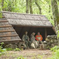 Big day out: Wildlife artist and environmentalist Robert Bateman (far left), his wife, Birgit, and Old Nic take shelter from the rain during the Batemans' recent visit to the woods of Nagano Prefecture. | C.W. NICOL