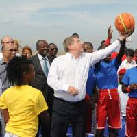 New opportunities: United Nations Secretary-General Ban Ki-moon (left) and IOC president Thomas Bach (center) play basketball with a group of students while touring the new facilities that were inaugurated on Tuesday at the Sport for Hope Centre in Port-au-Prince, Haiti. AFP-JIJI | AFP-JIJI