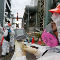 Walled off from future liability: A worker measures radiation in the air as employees prepare to attempt to create a frozen underground wall to surround the crippled reactor buildings at the Fukushima No. 1 nuclear plant earlier this month. | BLOOMBERG