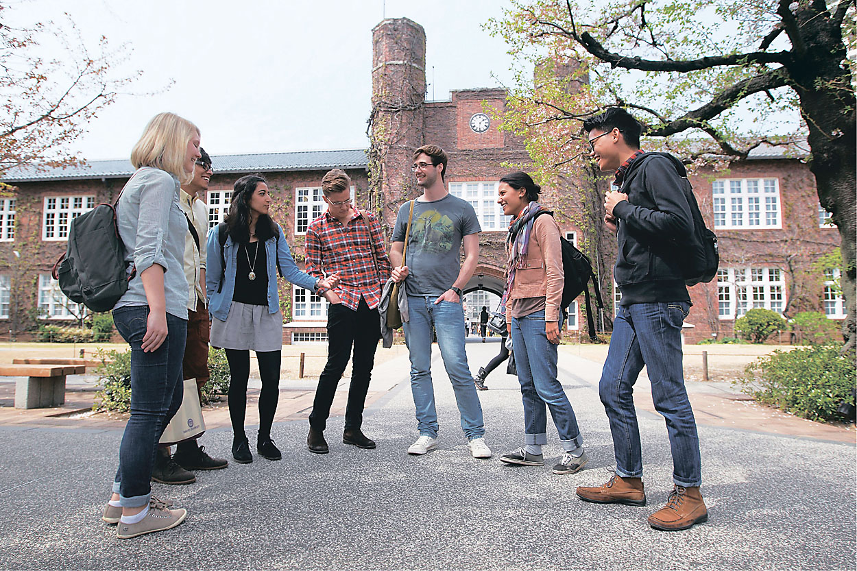 A group of students talk in front of Morris Hall, one of Rikkyo University