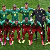 Searching for truth: Cameroon's national team poses for photos before facing Brazil in its final match at the 2014 World Cup on Monday. | AFP-JIJI