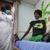 A newly diagnosed HIV-positive woman, who arrived at a hospital with symptoms of tuberculosis, receives treatment on Feb. 27 at the Mildmay Uganda clinic in Kampala. The number of people living with HIV worldwide has remained virtually unchanged in the past two years and AIDS-related deaths are at their lowest since peaking almost a decade ago, according to a report from the United Nations AIDS agency released Wednesday. | AP