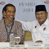 Indonesian presidential candidates Prabowo Subianto (right) and Jakarta Gov. Joko Widodo shared a light moment June 1 prior to drawing the electoral number that would represent them in the presidential election. | AP