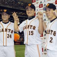 Three Musketeers: Giants players Yoshinobu Takahashi (left), Hirokazu Sawamura (center) and Hirokazu Ibata pose for pictures after their hero interview following Yomiuri's victory over Chunichi on Sunday. | KYODO