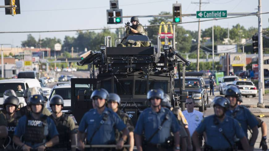 Riot police stand guard as demonstrators protest the shooting death of teenager Michael Brown in Ferguson, Missouri.