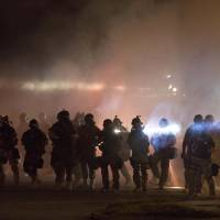 Riot police clear demonstrators from a street in Ferguson, Missouri, Wednesday evening after firing several rounds of tear gas on the fourth night of demonstrations. | REUTERS
