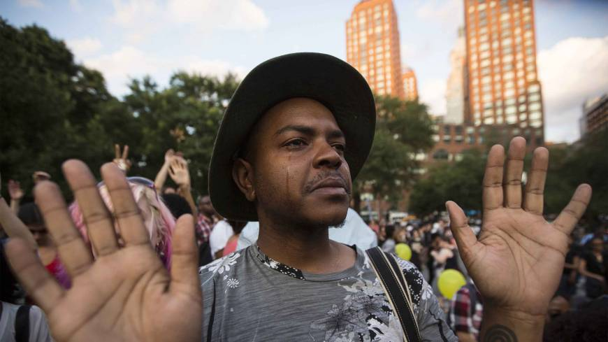 A man holds his hands up during a peaceful demonstration, as communities react to the shooting of Michael Brown in New York's Union Square Park Thursday.