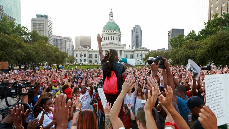 A speaker solicits a response of hands in the air from the crowd Thursday, in St. Louis during a peace vigil and moment of silence for Michael Brown, an unarmed teenager who was shot and killed by Ferguson, Missouri, police Saturday.
