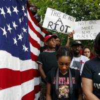 Vigil participants observe a moment of silence at Meridian Hill Park, also known as Malcom X Park, Thursday, in Washington, to protest the fatal shooting of Michael Brown by police in Ferguson, Missouri. | AP