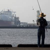 A couple fish in front of a tanker berthed at Tokyo Electric Power Co.'s Futtsu gas-fired thermal power plant in Futtsu, Chiba Prefecture, on July 21. Government policy to drive the yen down has raised import prices but hasn't boosted exports or the overall economy, pundits say. | BLOOMBERG