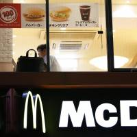 Customers are seen through the windows of a McDonald's store in Tokyo on Thursday. | REUTERS