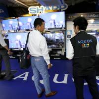 Shoppers look at Sharp Aquos televisions on display at an electronics store in Tokyo on Friday. | REUTERS