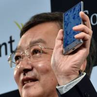 The president of Sharp, Kozo Takahashi, unveils a slender new smartphone called Aquos Crystal, on Monday. It has a 5-inch frameless LCD display and a Harman Kardon audio system. | AFP-JIJI