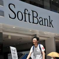 Pedestrians walk past a shop of Japanese mobile communications giant Softbank Corp. in Tokyo on Wednesday. | AFP-JIJI