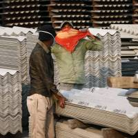 A worker covers his face with a handkerchief as he sees people photographing him and a coworker handling asbestos sheets at the Ramco Industries Ltd. factory in the Bhojpur district of India's Bihar state on Nov. 23 last year. | AP