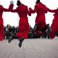 Hostesses jump for photographers outside Beijing's Great Hall of the People, where the opening session of the annual National People's Congress is held, on March 5, 2012. | AP