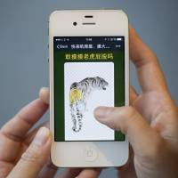 A screen from the WeChat game 'Brave enough to touch the tiger's butt?' is displayed on an iPhone 5 in Hong Kong on Friday. The mere fact that the messaging application's 400 million users can access the game reflects how discussion of Zhou Yongkang's fate is no longer taboo, and may even be encouraged, as the Communist Party builds support for a case against him. | BLOOMBERG