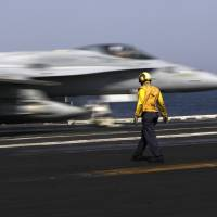A U.S. F/A-18 fighter jet takes off for Iraq from the flight deck of the USS George H.W. Bush aircraft carrier in the Persian Gulf on Monday. | AP