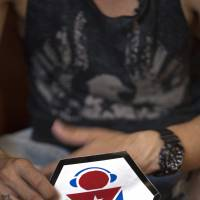 Manuel Barbosa, 25, shows the logo of his 'Revolution' audiovisual project during a July 11 interview in Santa Clara, Cuba. | AP