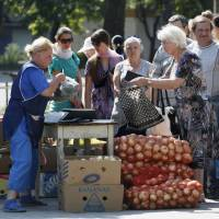 Passengers stand in line to buy vegetables Sunday in the eastern Ukrainian city of Donetsk. | REUTERS