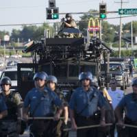 Riot police stand watch as demonstrators protest the shooting death of teenager Michael Brown in Ferguson, Missouri, on Wednesday. | REUTERS