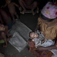 Roshida Beugam cradles her 3-month-old child, who already has signs of malnutrition, at her family's makeshift tent in a camp for Rohingya north of Sittwe in Myanmar, on June 25. | AP